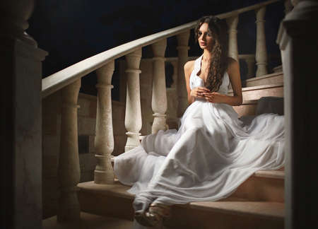 castle interior: Beautiful, emotional, sexy lady, woman sitting on stairs in dark castle interior. Silk white dress.