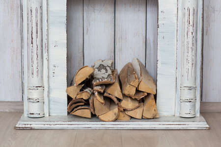 hearth and home: Vintage white fireplace with firewood in the studio