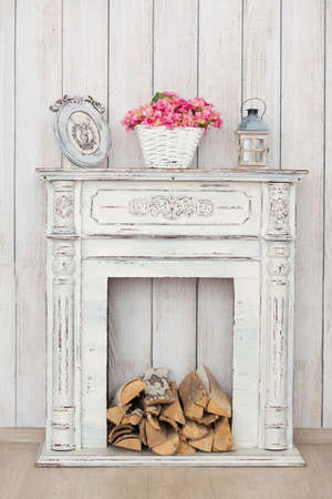 hearth and home: Vintage white fireplace with firewood and lamp