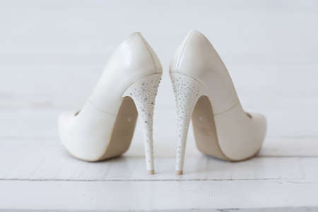 Chaussures blanches de mariage avec des paillettes sur un fond blanc.