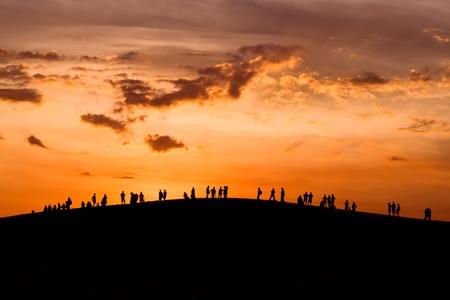 siluetas de enamorados: Grupo de personas disfrutando de la puesta de sol en la colina Foto de archivo