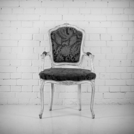 Vintage chair against a brick wall. Black and white photo
