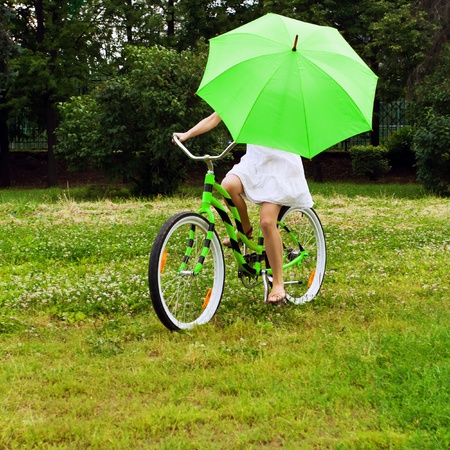 off road biking: Woman riding bicycle with a green umbrella Stock Photo