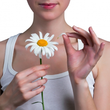 amorousness: Young girl guesses on a chamomile flower. Young girl tears off petals of daisy.  Stock Photo