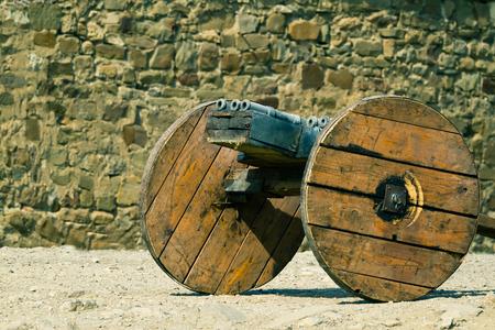 bombard: Medievale cannone multi-canna contro il muro di pietra di antica fortezza italiana