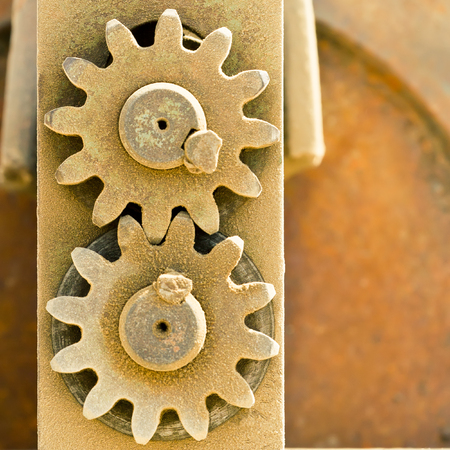 Old metal cog gears meshing together photo