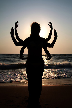 Girls silhouettes standing at the beach with arms raised up  Yoga practice outdoor photo