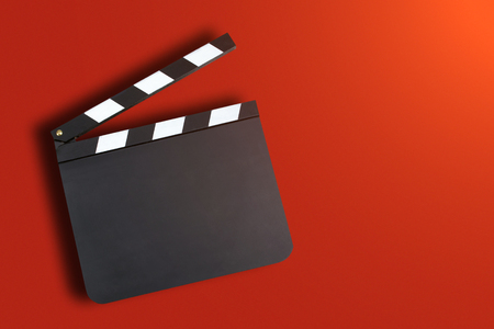 Blank movie production clapper board over red background with copy space