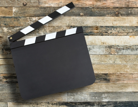 Blank movie production clapper board over wooden background with copy space  版權商用圖片