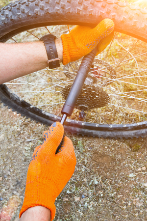Closeup of mechanic pumping a bicycle tire. Toned image photo