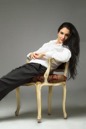 mujeres elegantes: Mujeres elegantes sentado contra el fondo gris