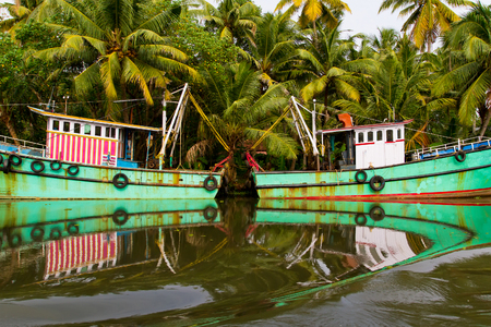 fishingboats: Indian fishing-boats with beautiful reflections in the water at famous backwaters of Kerala. Kochi, Kerala, India.