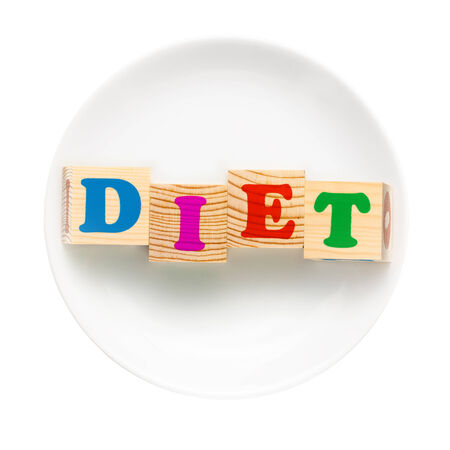 White plate with word diet composed of wooden cubes. Isolated on a white background. Dieting concept photo