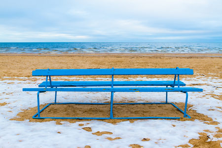 Winter view of a beach. Park bench on a winter beach. photo