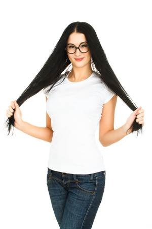 Young woman touching her long hair. Thinking about haircut concept. Smiling girl with blank white t-shirt isolated on a white background. photo