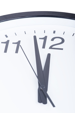 Clock face showing hands at two minutes to midnight. Focus on twelve Stock Photo