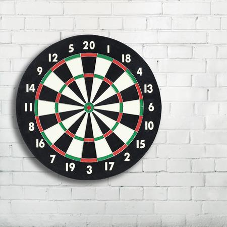sectores: Tarjeta de dardos en una pared de ladrillo blanco, con copia espacio. Tablero de dardos cl�sico con veinte sectores en blanco y negro