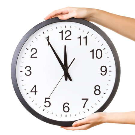 clockwise: Woman holding a big clock isolated on a white background. Anti clockwise or counter clockwise time concept