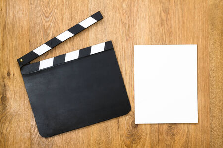 Blank movie production clapper board with blank paper against wooden background photo