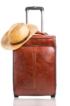 それが白い背景に対して分離された編みこみの帽子と革のスーツケース。旅行の概念