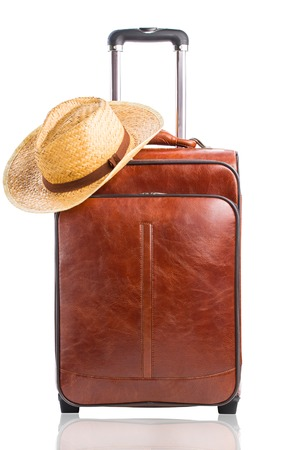 Leather suitcase with braided hat on it isolated against a white background. Travel concept