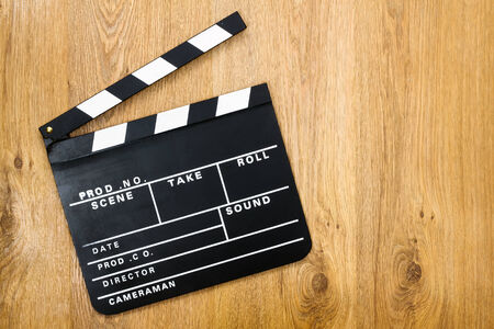 Movie production clapper board against wooden background with copy space photo