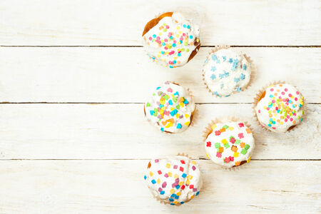 Tasty cupcakes on a white wooden background. Top view