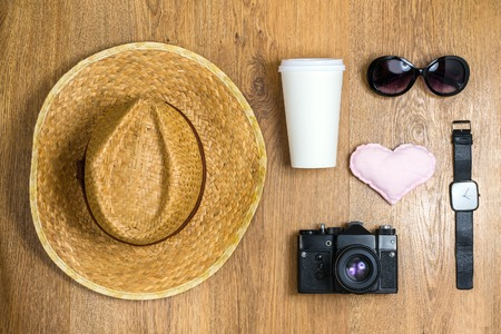 Top view of braided hat, pair of glasses, vintage camera, takeaway cup, watch and cute cloth heart on a wooden background. Travel concept