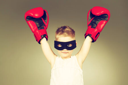 boxing boy: Boxing kid whearing black mask with hands raised up. Toned image Stock Photo