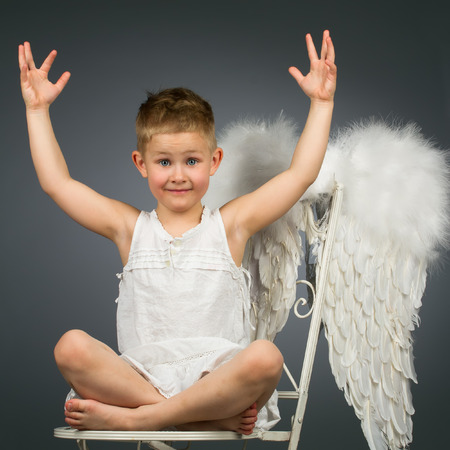 Happy kid with arms raised up sittig with white wings photo