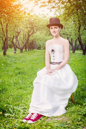Smiling bride wearing sneakers and retro hat sitting in summer park  Toned image photo