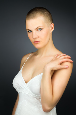 skinhead: Young woman with shaved hairstyle against dark background