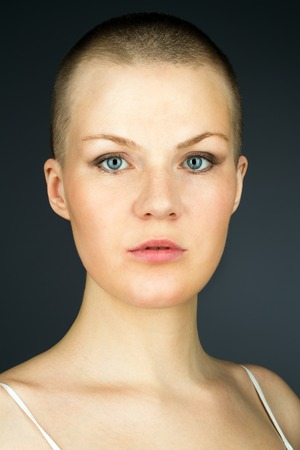 Portrait of young woman with shaved hairstyle against dark background  photo
