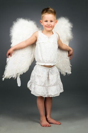 Happy angel kid standing with white wings photo