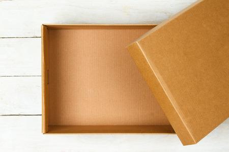 Geopend kartonnen doos op een houten tafel