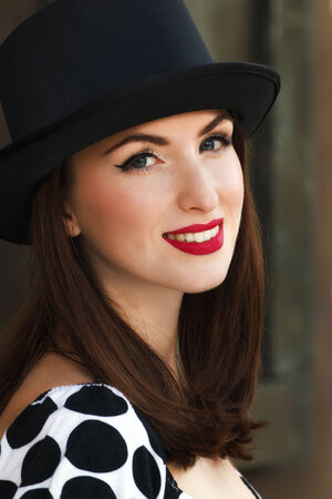 headshots: Smiling young woman wearing top hat