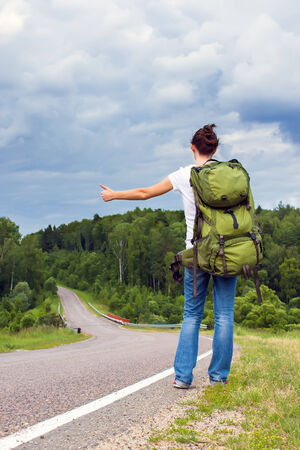 Woman with backpack hitchhiking on a country road photo
