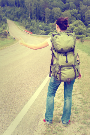 Woman with backpack hitchhiking on a country road. Toned image photo