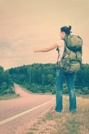 Woman with backpack hitchhiking on a road. Toned image photo