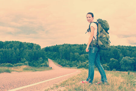 Woman with backpack on a country road. Toned image photo