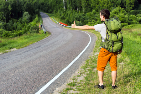 Man with backpack hitchhiking on a country road photo