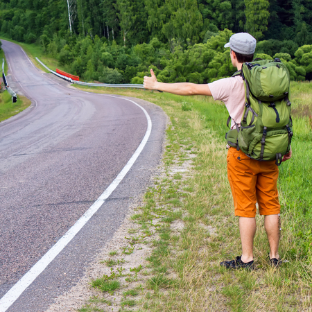 Man with backpack hitchhiking on a road photo