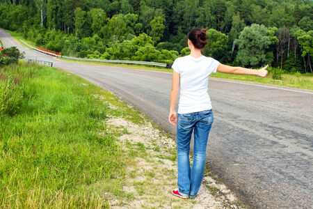 Woman hitchhiking on a road photo