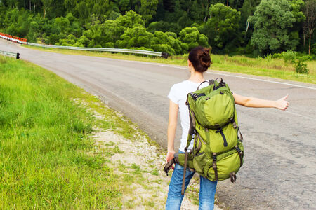 Young woman with backpack hitchhiking on a road photo