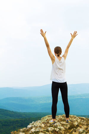 Happy woman with arms raised up photo