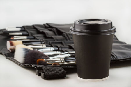 Coffee cup and makeup brushes. Coffee break from work - concept photo