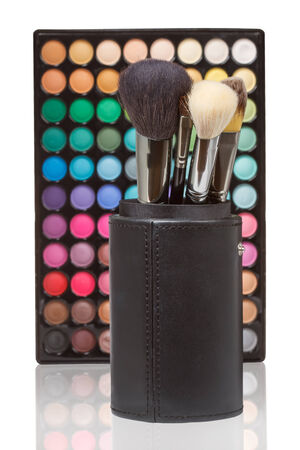 Makeup brushes against makeup palette on a white background photo