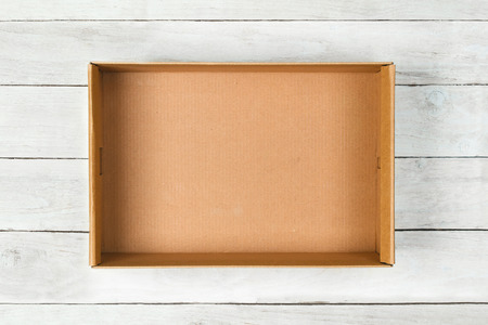 Cardboard box on a white wooden  Stockfoto