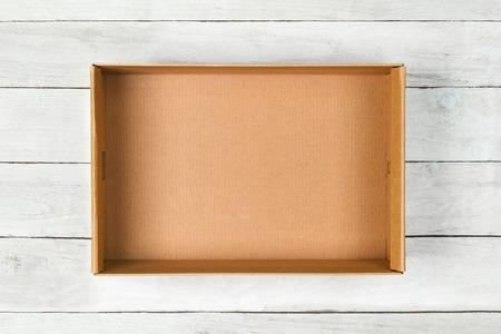 Cardboard box on a white wooden  Archivio Fotografico