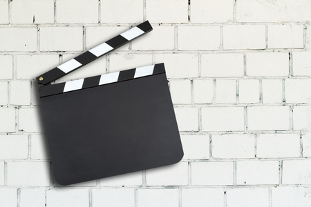 Blank movie production clapper board against a brick wall